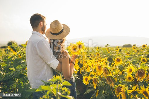 Couple enjoying summer time at sunflowers field