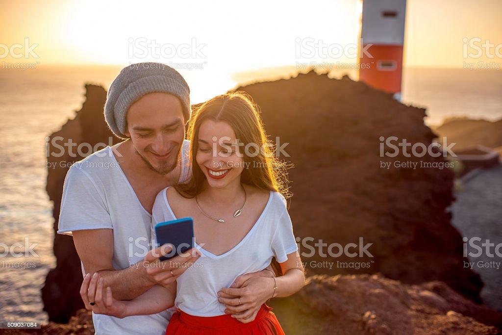 Couple enjoying summer vacation near the lighthouse stock photo