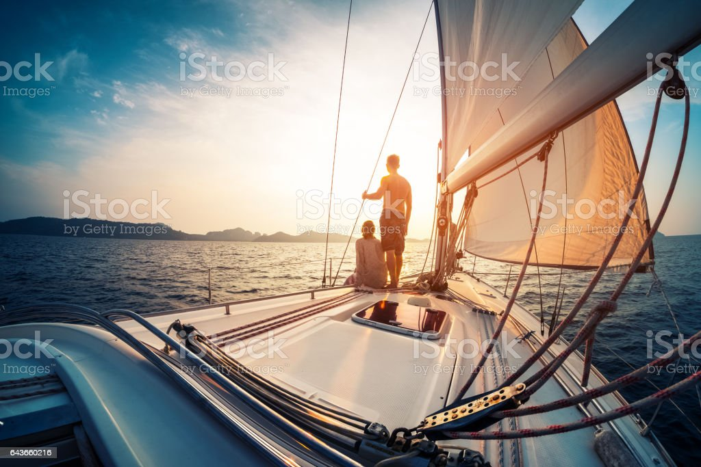 Couple enjoying sunset from the sail boat stock photo