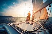 帆ボートからの夕日を楽しむカップル