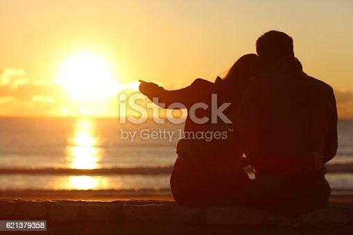 492610640istockphoto Couple enjoying sunset on the beach in winter 621379358