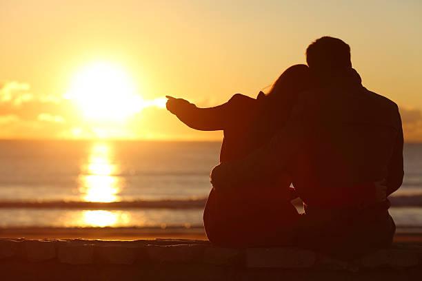 couple enjoying sunset on the beach in winter - romantische strand fotos stock-fotos und bilder