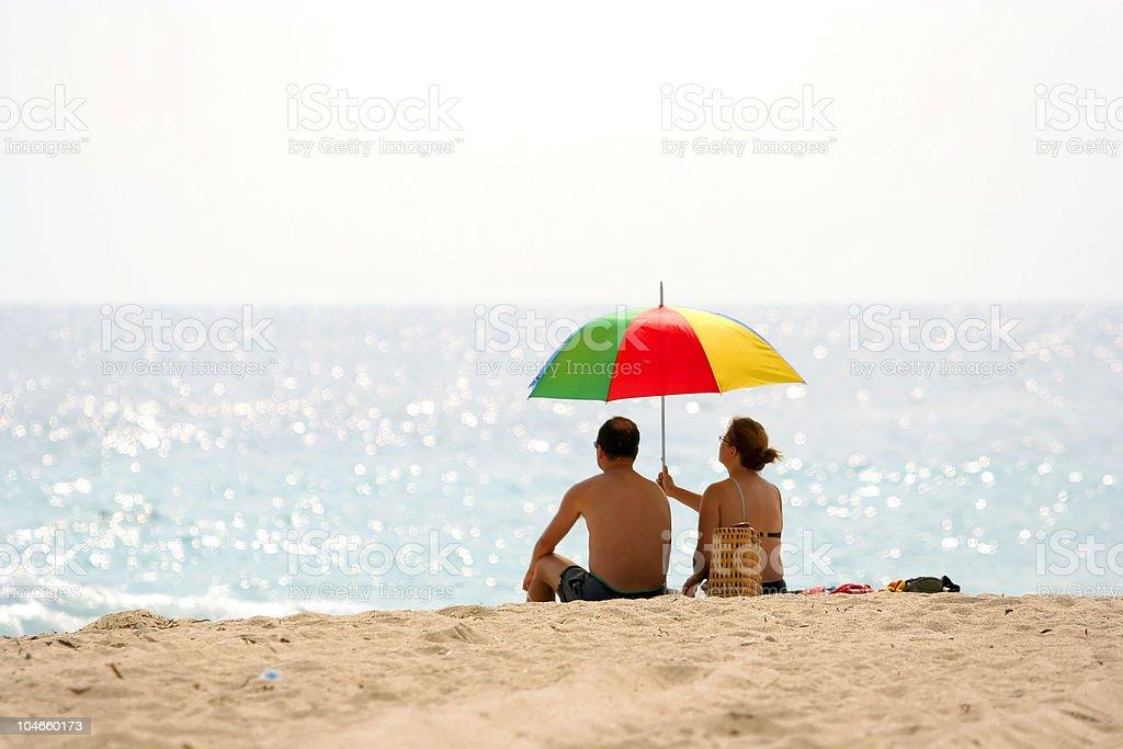 Couple enjoying the beach. Umbrella. Summer. Outdoor. Happy. Holiday. stock photo