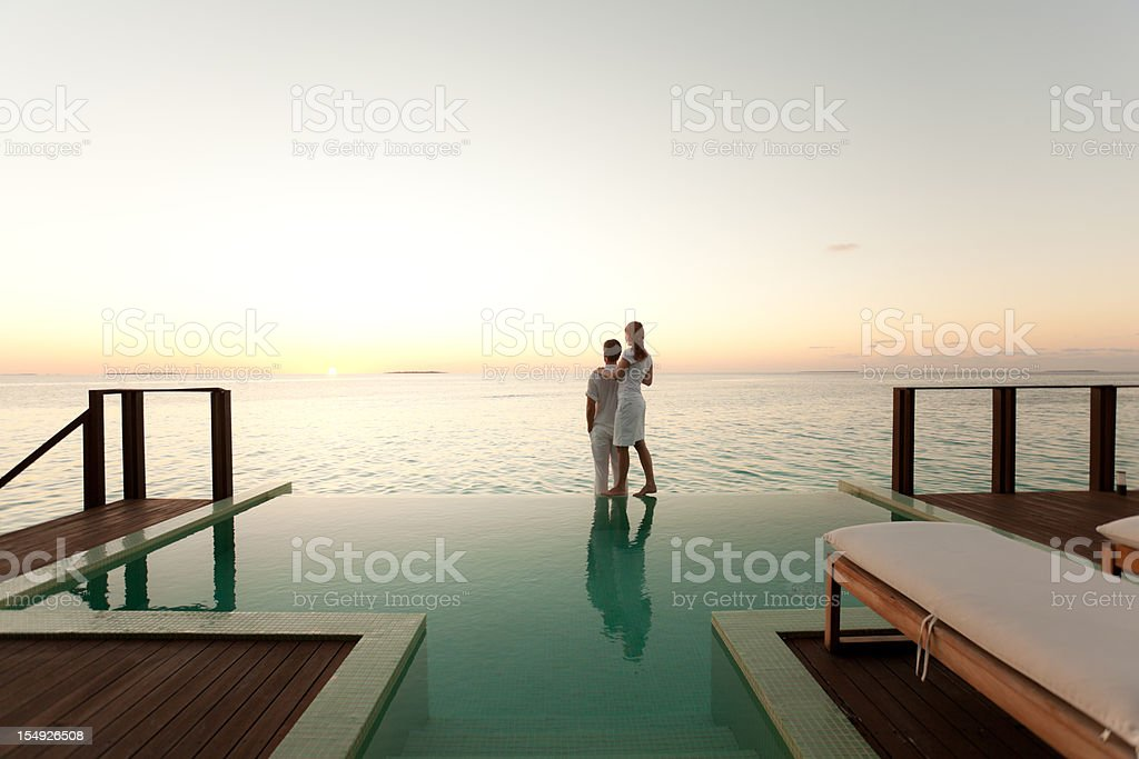 Couple enjoying the sunset at poolside stock photo