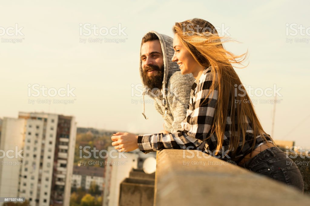 Ein paar genießt den Sonnenuntergang in der Stadt auf dem Dach – Foto