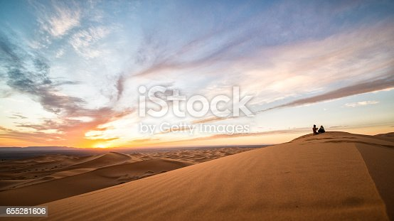 istock A couple enjoying the sunset on the dunes of the Sahara Desert in Merzouga - Morocco 655281606