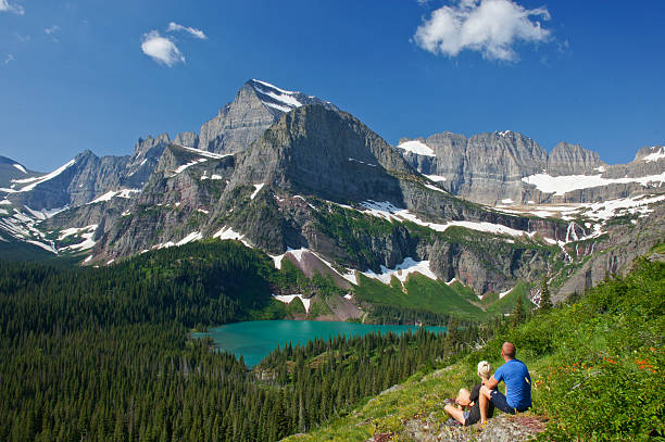 couple enjoying the view in glacier national park - us glacier national park stock pictures, royalty-free photos & images