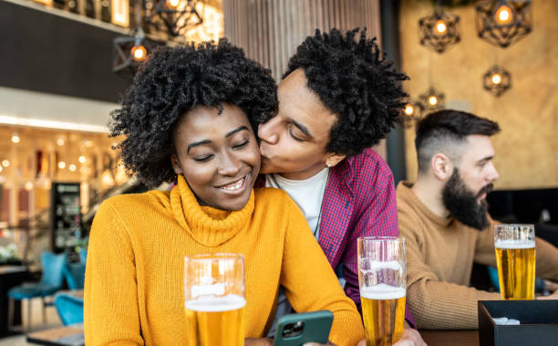 A couple enjoying their day in the bar, with their two  friends. stock photo