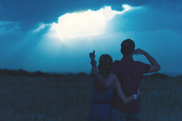 couple enjoying under the moonlight in nature. my astronomy work. - romantic moon stock photos and pictures