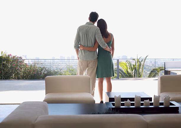 Couple enjoying view from balcony stock photo