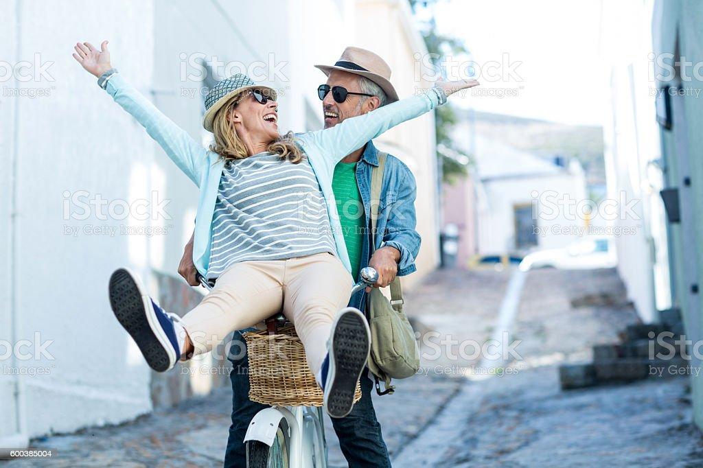 Couple enjoying while riding bicycle stock photo