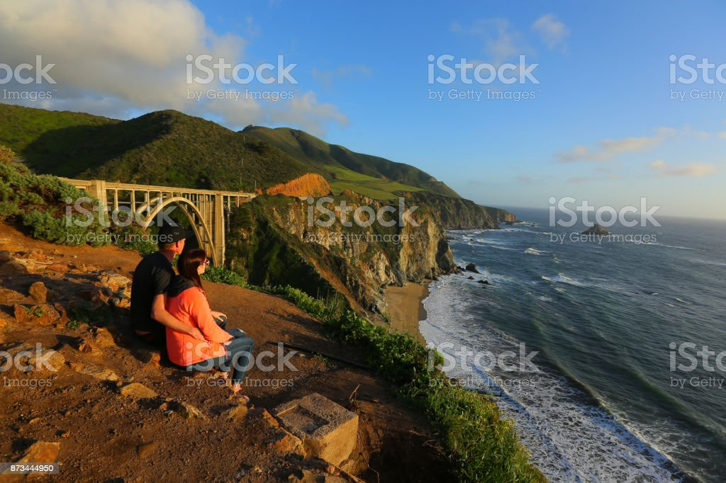 couple enjoys a view of sunset stock photo