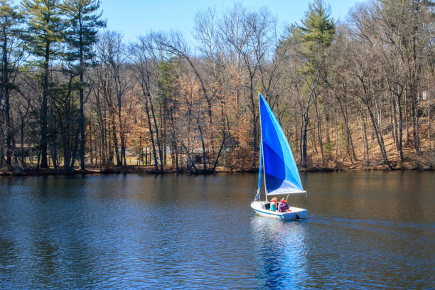 Windsor, Connecticut, USA - March 31, 2018: A couple enjoys an early spring day by sailing on Rainbow Reservoir stock photo