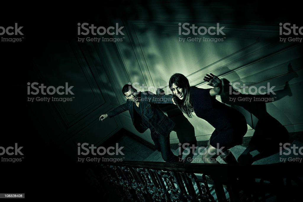 couple escaping from evil stock photo