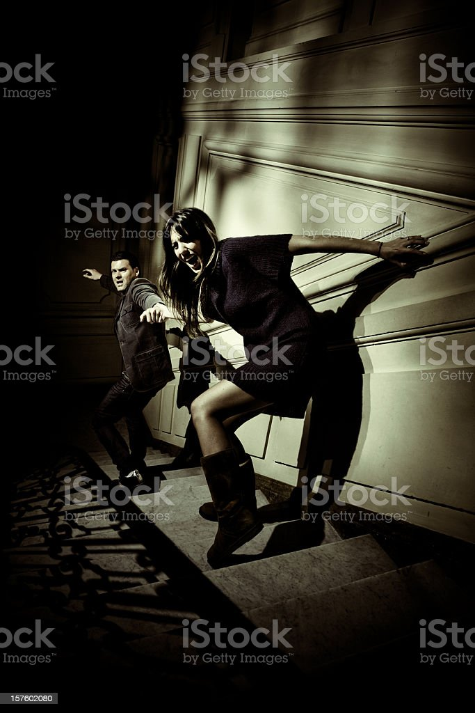couple escaping from something evil stock photo