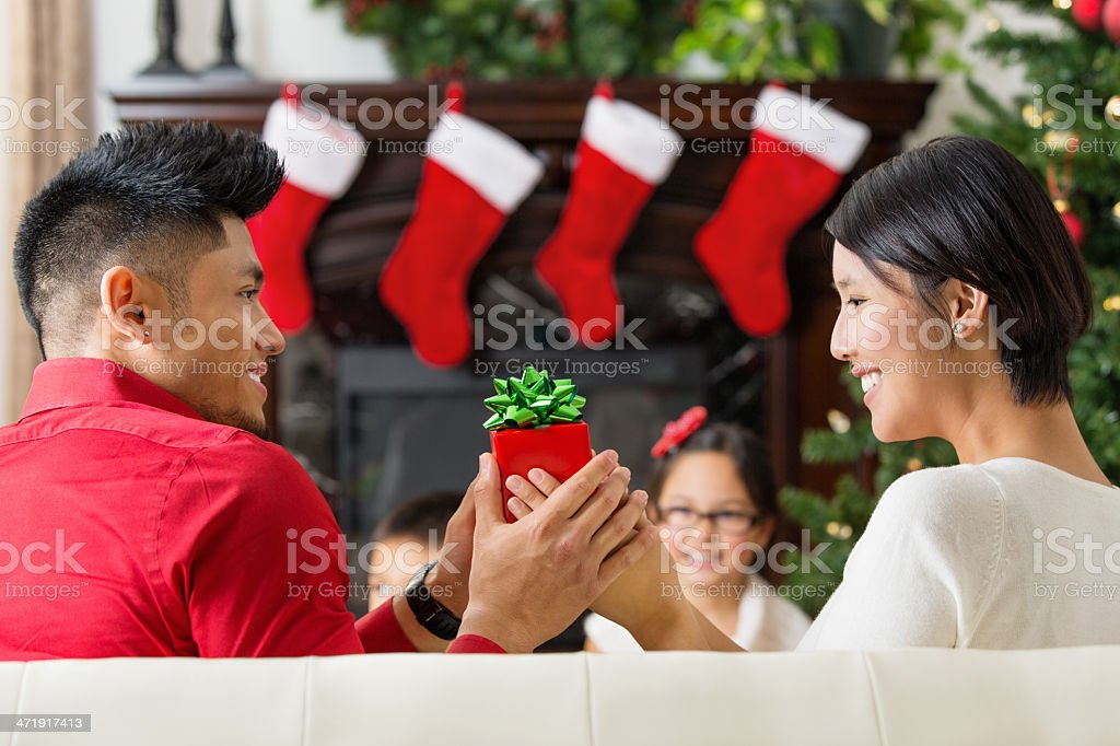 Couple exchanging Christmas gifts at home stok fotoğrafı
