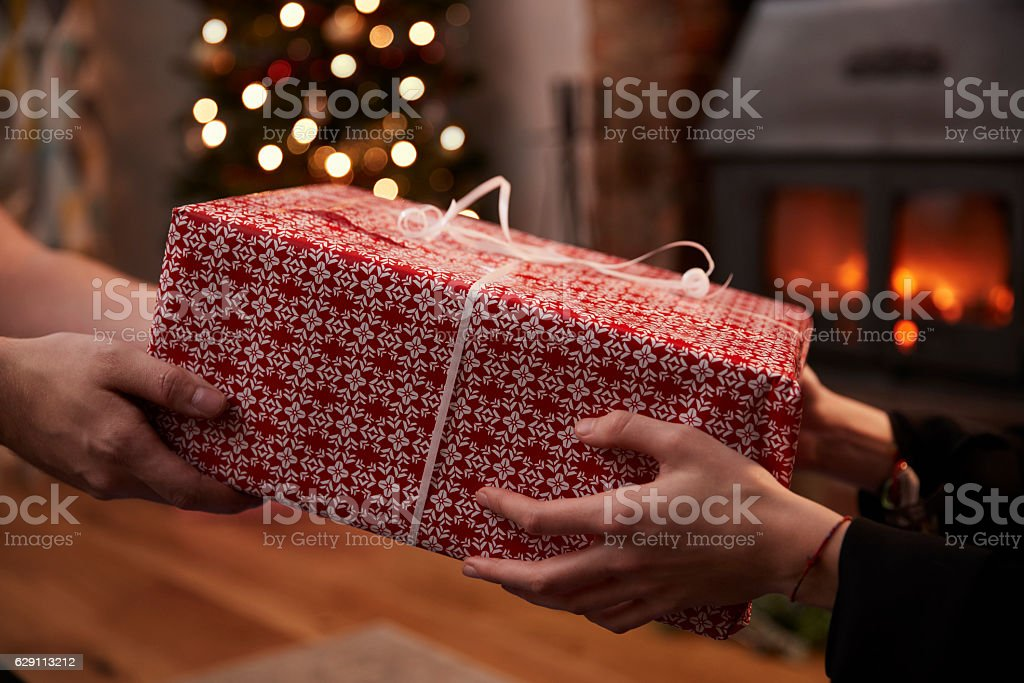 Couple Exchanging Gifts In Room Decorated For Christmas – Foto