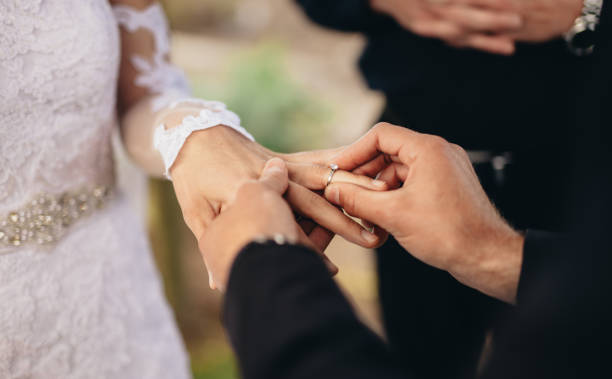 Couple exchanging wedding rings Closeup of groom placing a wedding ring on the brides hand.  Couple exchanging wedding rings during a wedding ceremony outdoors. bridegroom stock pictures, royalty-free photos & images