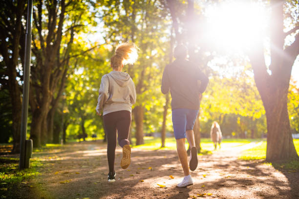 couple exercising in park. - jogging stock pictures, royalty-free photos & images