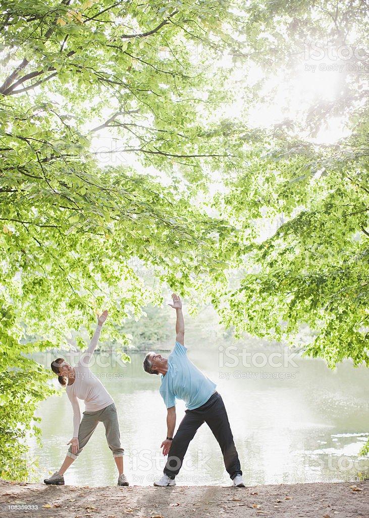 Couple exercising near lake stock photo