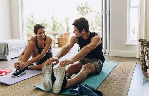 Couple exercising together at home Couple exercising together. Man and woman in sports wear doing workout at home. jacoblund stock pictures, royalty-free photos & images