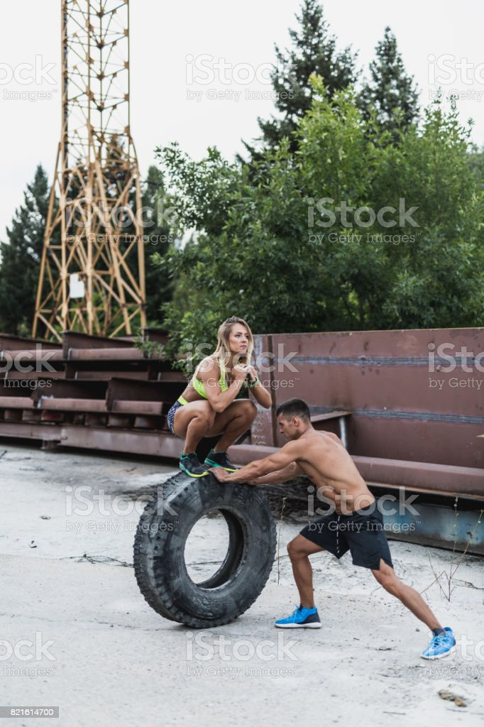 Couple exercising with an old tire stock photo