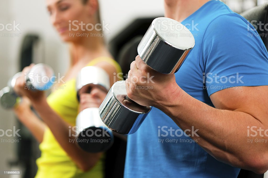 A couple exercising with Dumbbells in the gym royalty-free stock photo