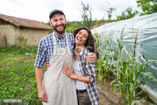 Cheerful farmers embracing and standing in greenhouse