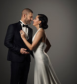 Couple Fashion Portrait, Elegant Man in Black Suit and Beautiful Woman in White Dress, Studio shot over gray background