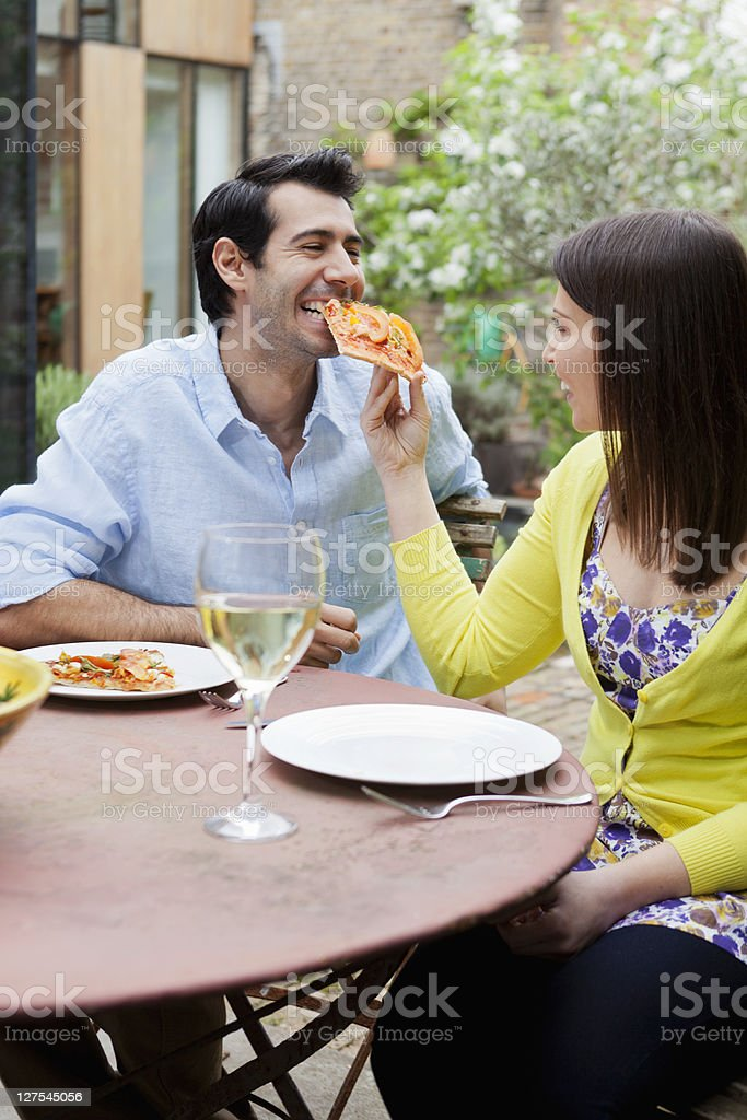Couple feeding each other pizza outdoors stock photo