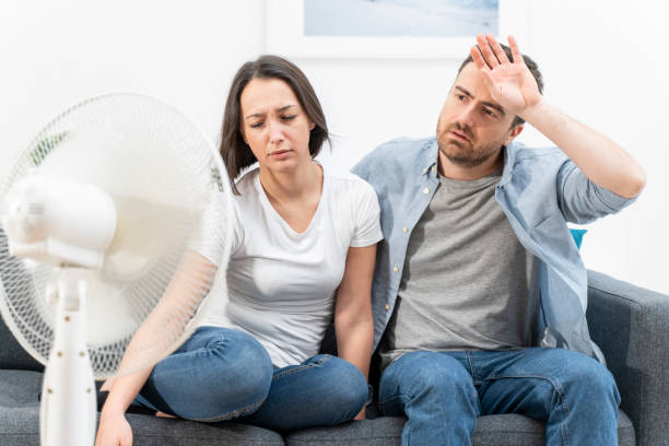Couple feeling bad at home after summer heat stock photo