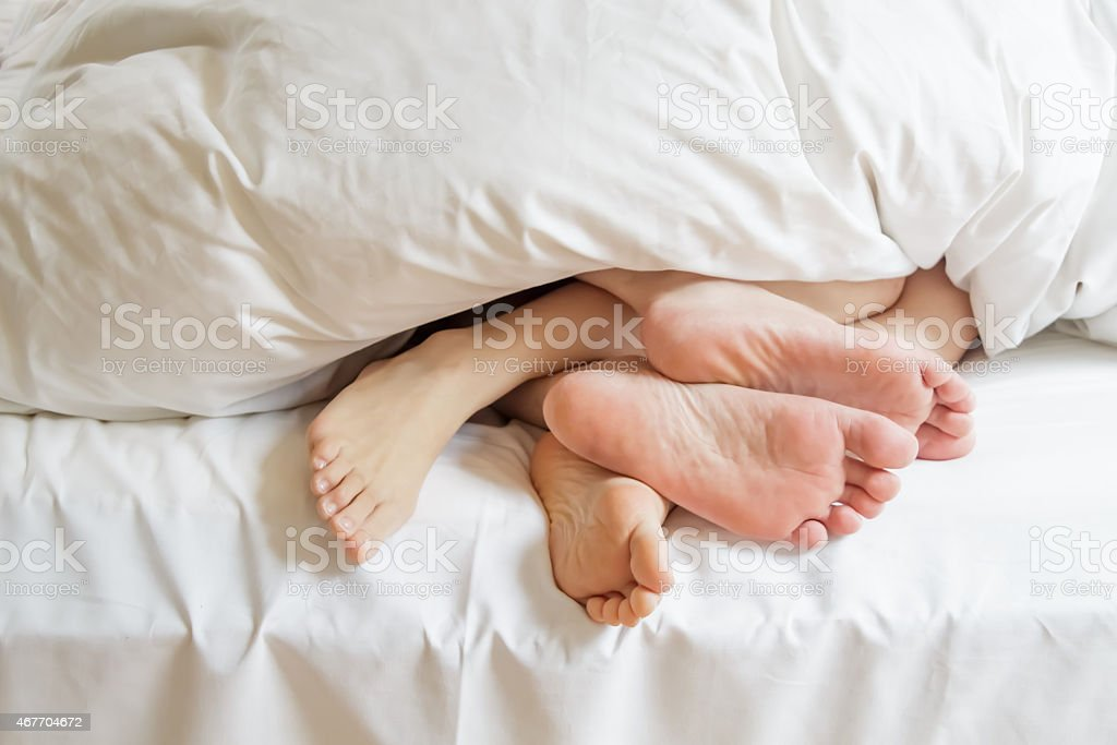 Couple feet in the bed stock photo