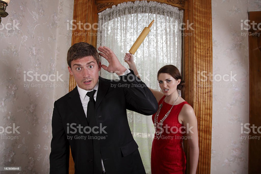 Couple Fighting - Man Chased By Woman With Rolling Pin royalty-free stock photo