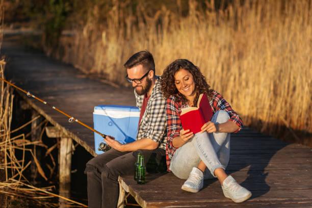 Couple fishing and reading at the lake docks stock photo