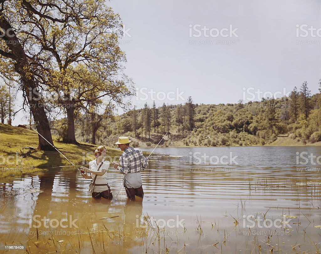 Couple fishing in lake, smiling stock photo