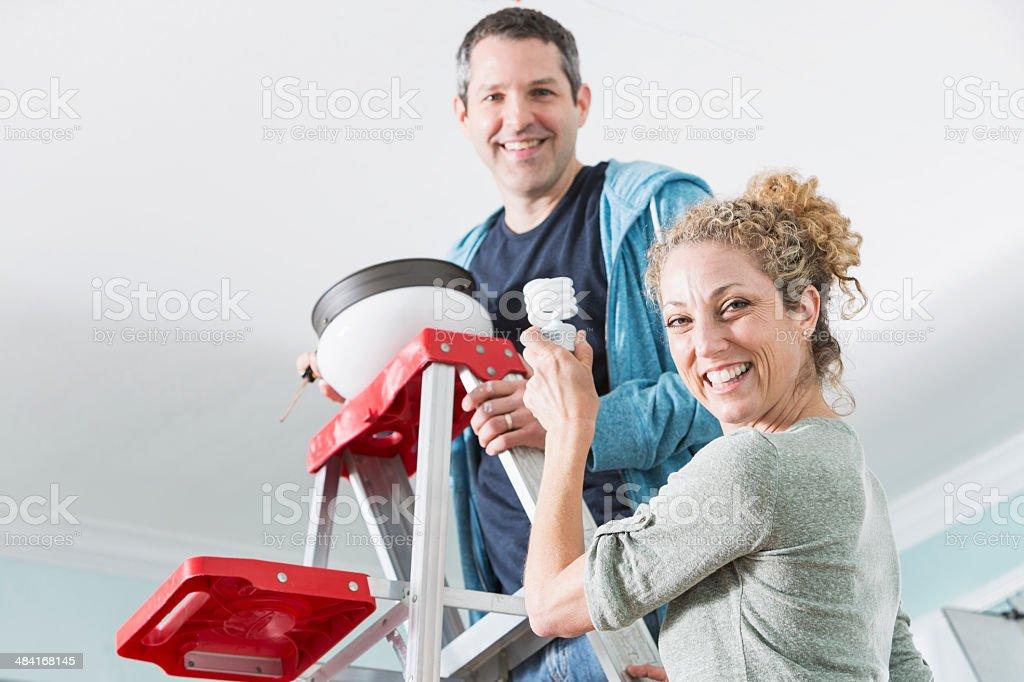 Couple fixing ceiling light stock photo