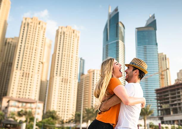 paar flirten auf die skyline von dubai marina - dubai urlaub stock-fotos und bilder