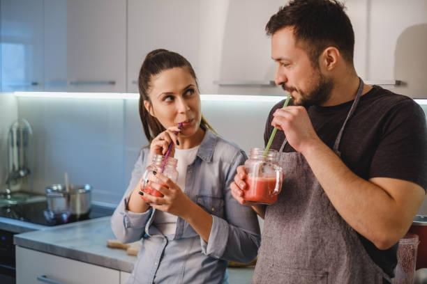 Pareja flirteo en la cocina bebiendo batidos - foto de stock