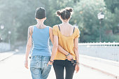 Rear view of two girlfriends having fun and walking on bridge. Both with casual clothes.