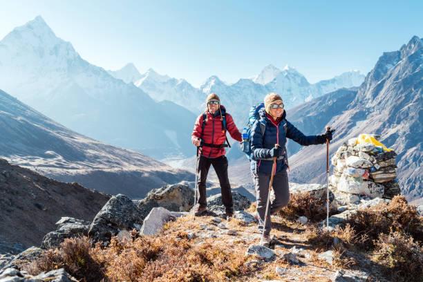 Paar folgt Everest Base Camp Trekkingroute in der Nähe von Dughla 4620m. Backpacker, die Rucksäcke mit sich führen und Trekkingstöcke benutzen und den Blick auf das Tal mit dem Gipfel Ama Dablam 6812m genießen – Foto