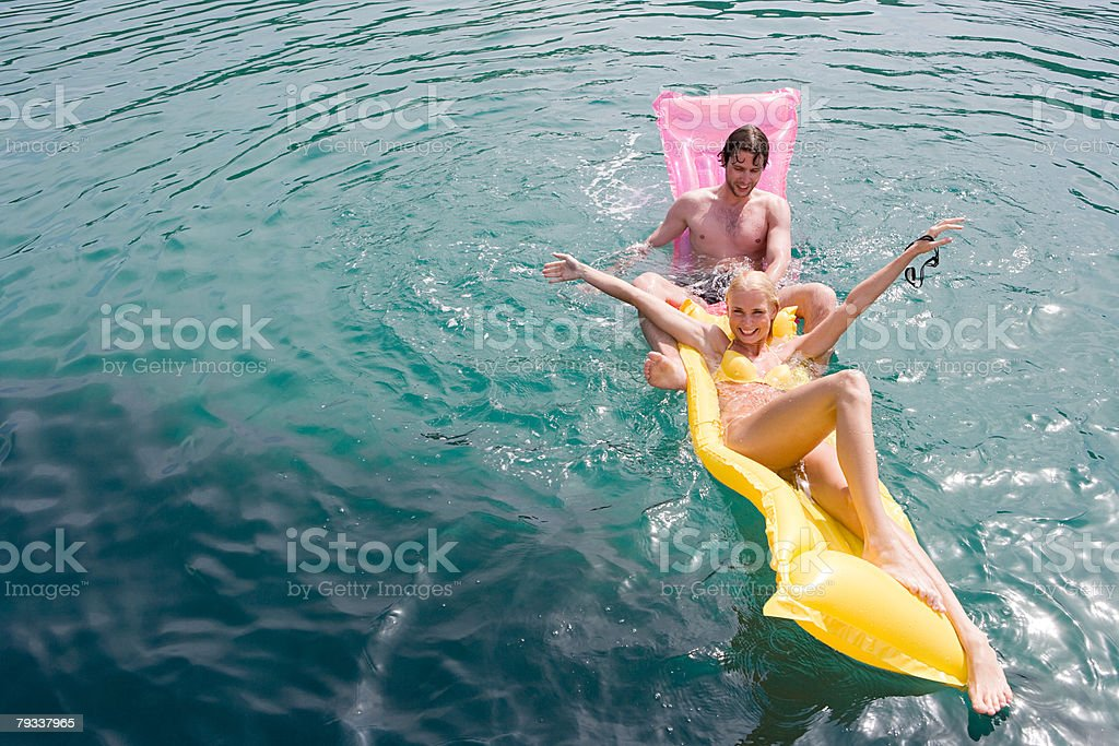 A couple fooling around on inflatable mattresses royalty-free stock photo