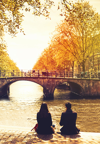 Couple friends or lovers relaxing on embankment of canal and looks at the river and bridges of Amsterdam. Photo toning at retro color. Spring or autumn time in the city. Travel Netherlands, Europe.