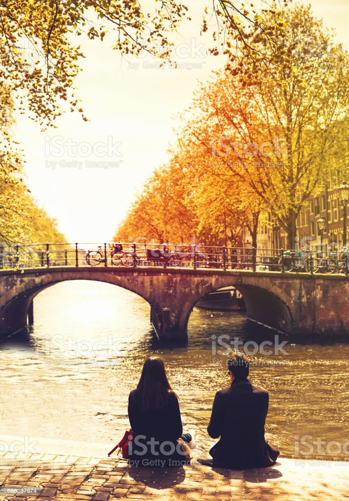 Couple friends or lovers relaxing on embankment of canal and looks at the river and bridges of Amsterdam. stock photo