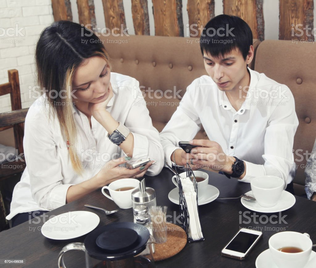 Couple from guy and girl have a cofee time in the cafe and looking on the phone stock photo
