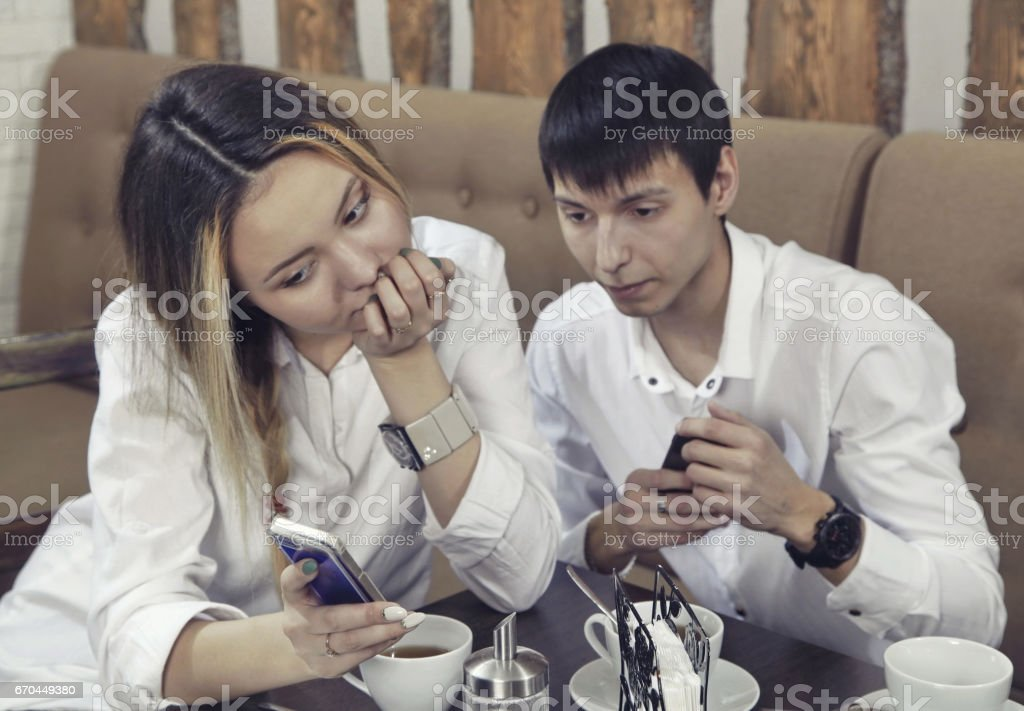 Couple from guy and girl have a tea time in the cafe and looking on the smartphone absorbedly with focus on the phone stock photo