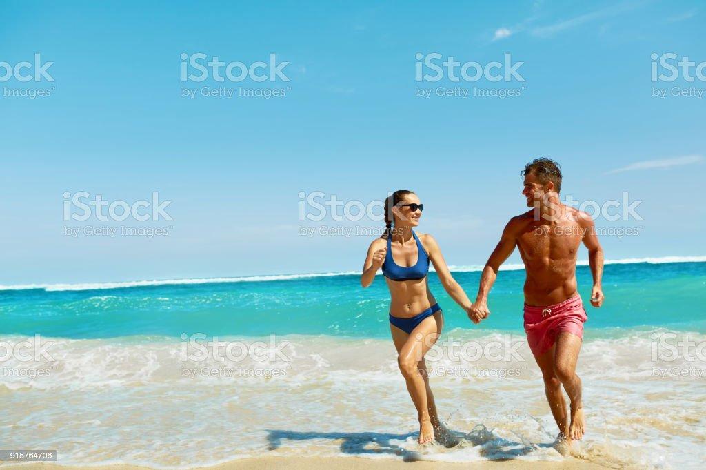Couple Fun On Beach. Romantic People In Love Running At Sea stock photo