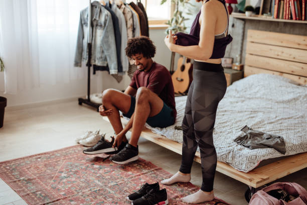 couple getting dressed for morning workout - men shoes stock pictures, royalty-free photos & images