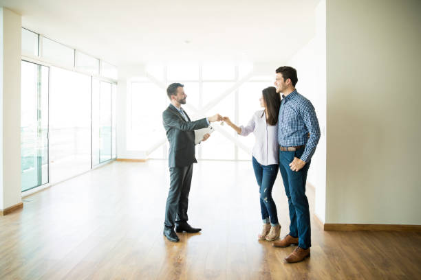 Couple Getting Keys From Realtor Of Their New Home stock photo
