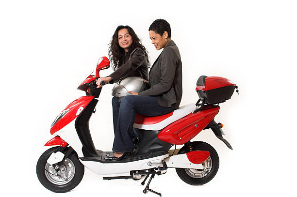 couple girls talking on  scooter stock photo