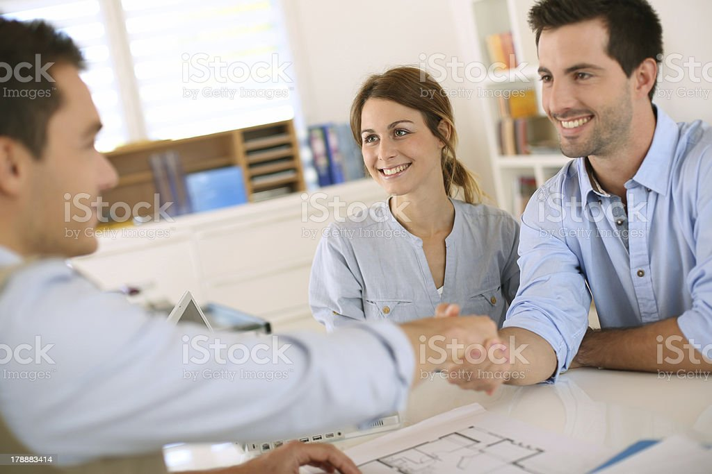 Couple giving agreement for starting work with shake hands royalty-free stock photo